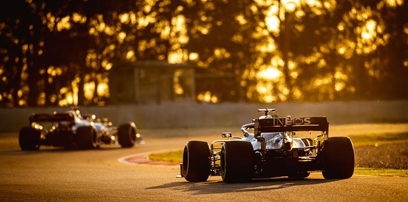 formula one cars racing at dusk time